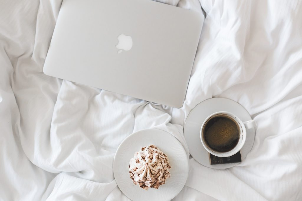 Coffee, Cake and Mac Book on White Bed sheets.